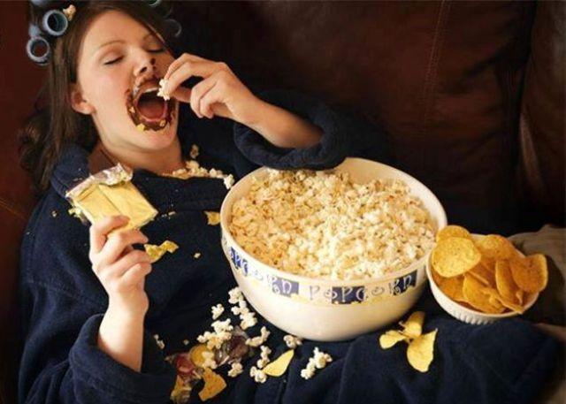 Femeie pe canapea care mananca junk food