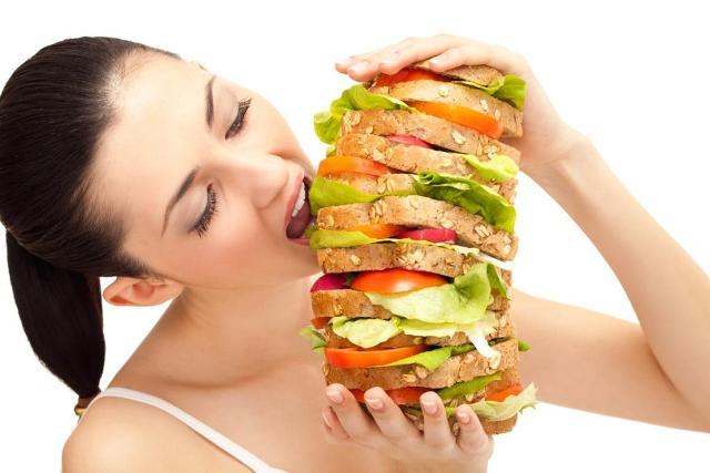 O femeie luand o gura dintr-un sandwich urias